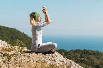 Beautiful blond yoga woman sitting on the top of the mountain in lotus pose. Meditation on the edge with a scenic view of the landscape and the sea.
