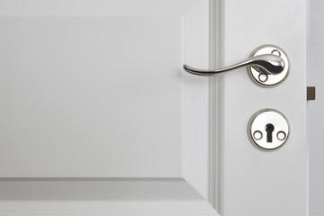 Metallic door knob on a classic white door. Home
