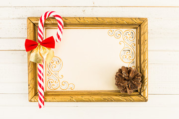 Blank picture frame with Christmas cane candy on wood