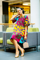 Intelligent african american princess woman wearing bright colorful national dress and gold hoes sitting in armchair in waiting hall by shopping center.