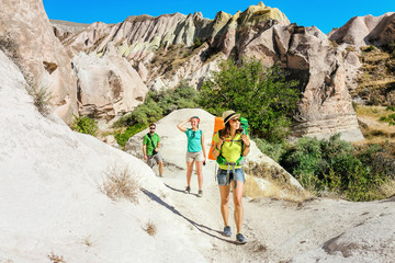 A group of young active and bright travelers walk among the desert colorful hills of tuff in the national park of Cappadocia, Turkey