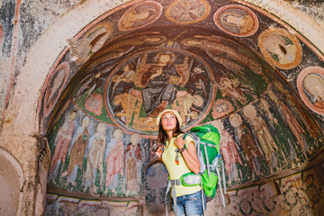 Woman traveler or archaeologist with a backpack admiring the arch of an ancient church with frescoes in Cappadocia