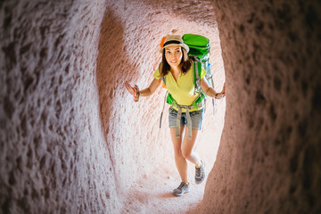 Traveler woman with backpack walking in cave underground city in Cappadocia, Turkey. Concept of archeology and tourist destination