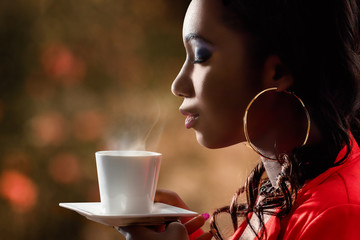 Attractive African woman smelling hot cup of coffee.