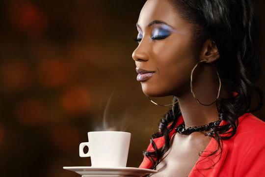 African woman smelling coffee with eyes closed.