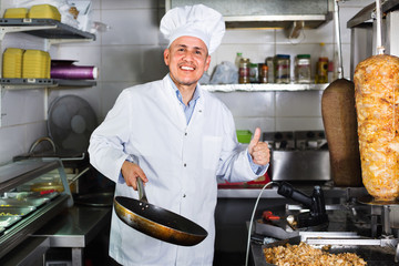Man cook making kebab dish and looking satisfied holding thumbs up