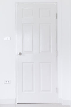 White door on white wall with stainless door knob,Handle on white wood door,Close Up white door interior