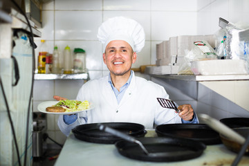 Smiling professional cook sitting on kitchen