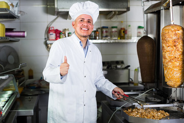 mature chef holding thumbs up on kitchen