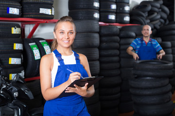 girl in workwear in auto mechanic workshop.