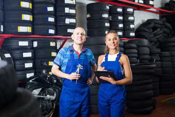 female technician in overalls holding clipboard  in car workshop