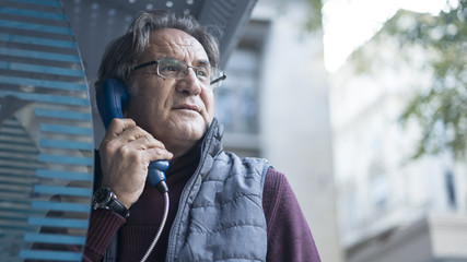 Senior man talking on public payphone in outdoors
