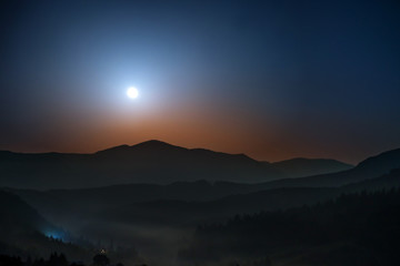 Moon rising above the mountains at night