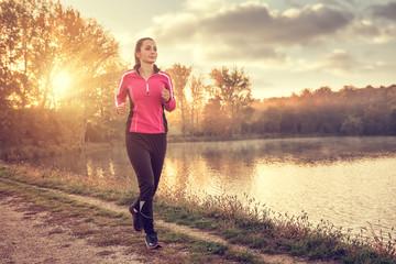 Beautiful young woman running at the lake