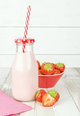 A bottle of strawberry yogurt milkshakes on a wooden table with fresh fruit and copy space