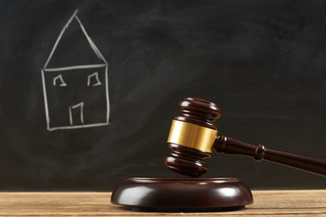 Judge gavel on wooden table at blackboard background with painted house.