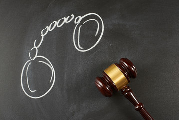 Judge gavel on blackboard background with painted .handcuffs.