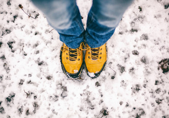 feet in yellow trekking boots on snow, a trip in winter, a picture from above