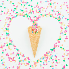 Heart symbol made of colorful bright confetti and waffle cone on white background. Flat lay, top view copy space. Love concept