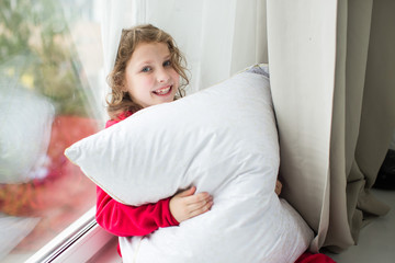 girl in red pajamas with a snow-white pillow