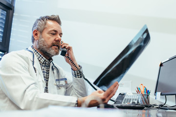 Doctor checking x-ray and talking on telephone at clinic