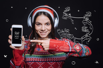Pay attention to this gadget. Cheerful positive young woman standing against imaginary drawing on the black wall and expressing happiness while listening to the music and pointing on the smartphone