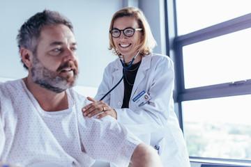 Medical examination of mature man in hospital ward