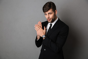 Close-up photo of handsome young man in black suit clap in hands, lookig at camera