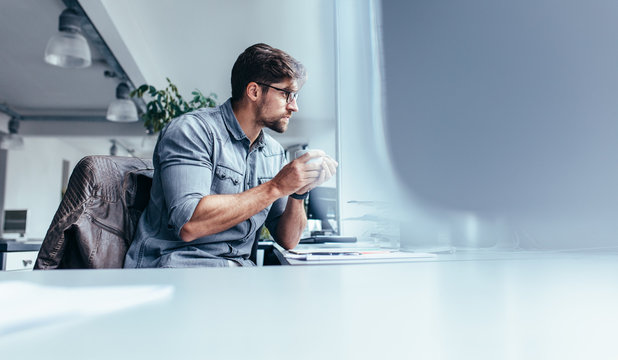 Businessman sitting in office with cup of coffee
