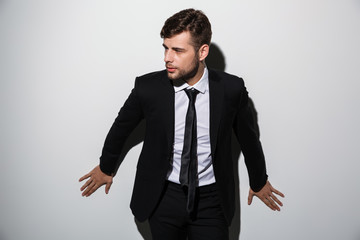 Handsome businessman in black suit posing and leaning at white wall