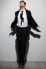 Full length portrait of young businessman with closed eyes jumping over white background