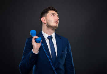 Young business man holding and talking on telephone
