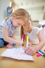 Zwei Kinder malen ein Bild auf Papier