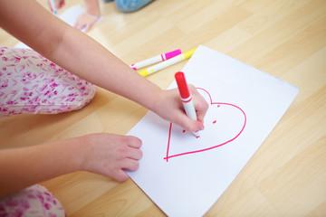 Hand von Kind malt rotes Herz
