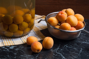 Fresh organic harvested apricots in steel colander and big glass jar with canned apricot compote on dark marble..