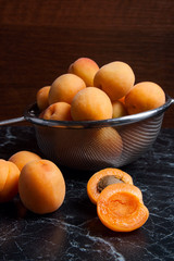 Fresh organic apricots in steel colander. Group of harvested apricots whole and halved in steel colander..