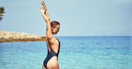 adult slim attractive woman posing in blue waters of Adriatic sea beach on Makarska riviera