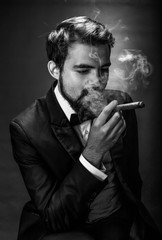 black and white portrait of bearded smoking gentleman in a suit perceptive looking at the cigar