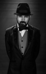 black and white portrait of bearded smoking gentleman in a suit with a butterfly and black hat