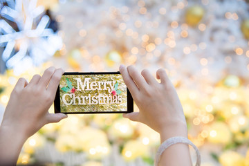 Girl's hand holding mobile phone take a photo of christmas tree with wording Merry Christmas. Young woman using smartphone outdoor capture picture of Christmas decoration with bokeh blur background.