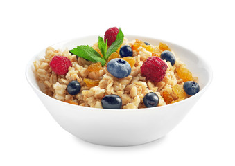 Tasty oatmeal with raisins and berries in bowl on white background