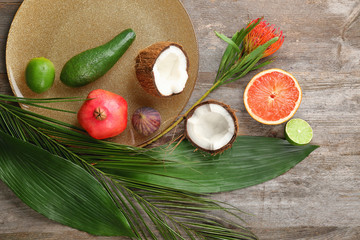Composition with tropical leaves and exotic fruits on table