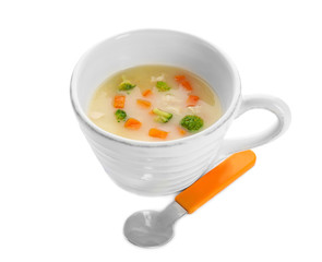 Mug with creamy soup for baby on white background