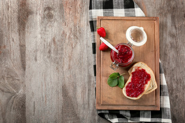 Jar and bread with strawberry jam on wooden board