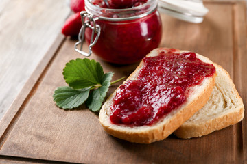 Bread and jar with strawberry jam on wooden board