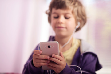 Little boy sitting on bed listening music on his smartphone. Selective focus.