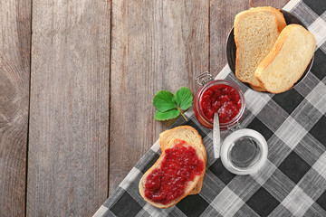 Bread and jar with strawberry jam on wooden table
