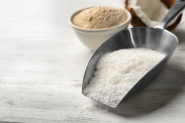 Scoop with desiccated coconut and flour in bowl on white background