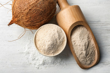Nut, scoop and bowl with flour on wooden table