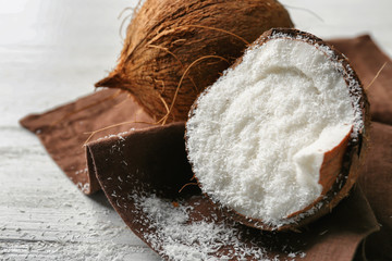 Desiccated coconut in nut on wooden table